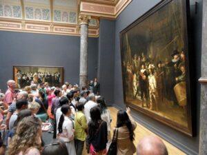 bezoekers drommen samen bij de Nachtwacht van Rembrandt